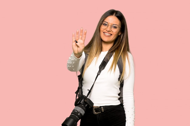 Young photographer woman happy and counting four with fingers on isolated pink background