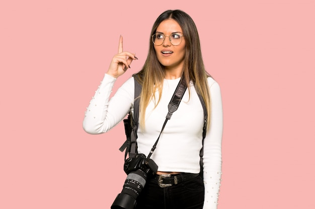 Young photographer woman intending to realizes the solution while lifting a finger up on isolated pink background