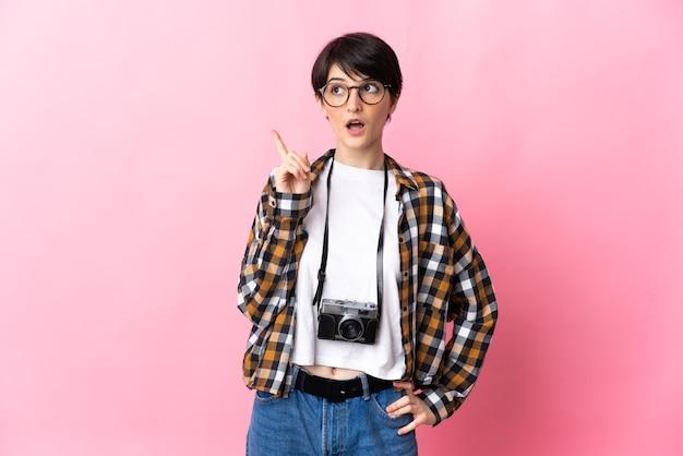 指を上に向けるアイデアを考えてピンクの壁に孤立した若い写真家の女性