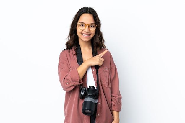 Молодая женщина-фотограф изолирована, указывая в сторону, чтобы представить продукт
