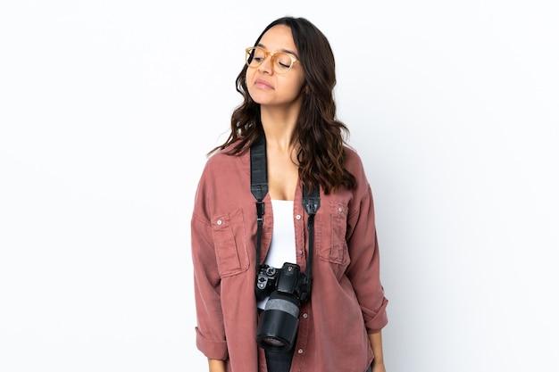 若い写真家の女性は、側を見ながら疑問を持っている白い背景を分離しました。