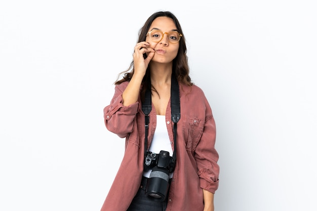 Young photographer woman over isolated white wall showing a sign of silence gesture