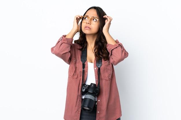 疑いと思考を持っている孤立した白い背景の上の若い写真家の女性
