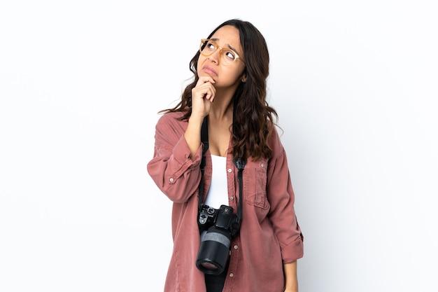 Молодая женщина-фотограф на изолированном белом фоне с сомнениями