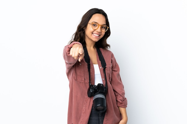Молодая женщина-фотограф на изолированном белом фоне, указывая спереди со счастливым выражением лица