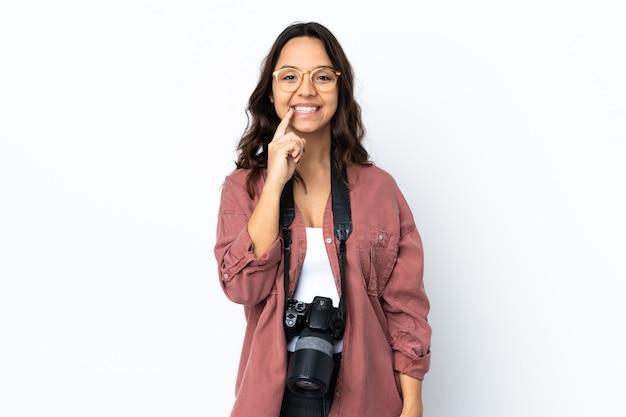 입에 손가락을 넣어 침묵 제스처의 기호를 보여주는 격리 된 흰색 배경 위에 젊은 사진 작가 여자