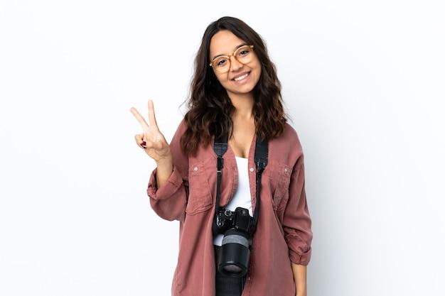 Молодой фотограф женщина на изолированном белом фоне улыбается и показывает знак победы