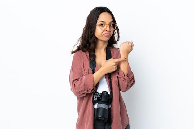Молодая женщина фотографа над изолированной белизной делая жест быть поздно