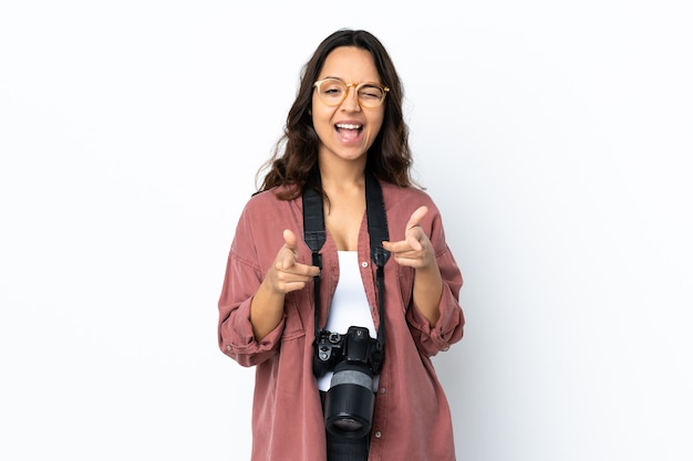 격리 된 흰색 전면을 가리키는 웃 고 젊은 사진 작가 여자