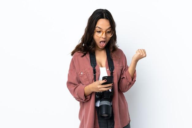 Молодой фотограф женщина над изолированным белым удивлен и отправляет сообщение