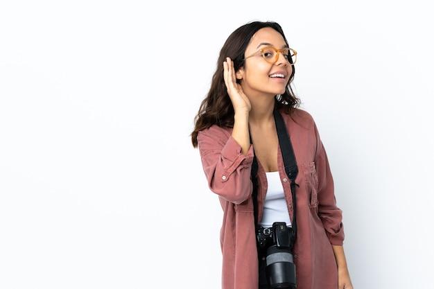 耳に手を置いて何かを聞いている孤立した白い壁の上の若い写真家の女性