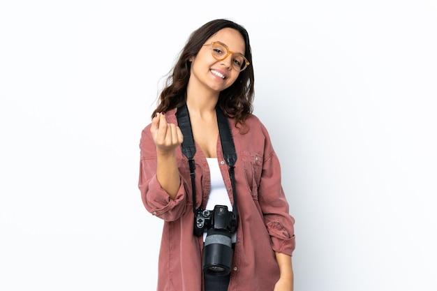 Молодая женщина-фотограф над изолированной белой стеной делает денежный жест
