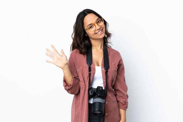 指で5つを数える白い壁の上の若い写真家女性