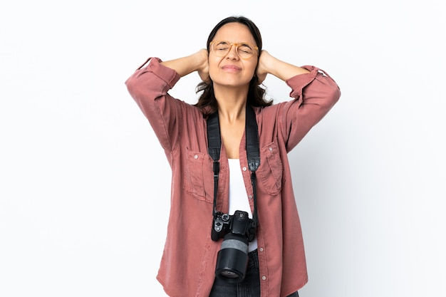 Молодой фотограф женщина над белой стеной разочарование и охватывающих уши
