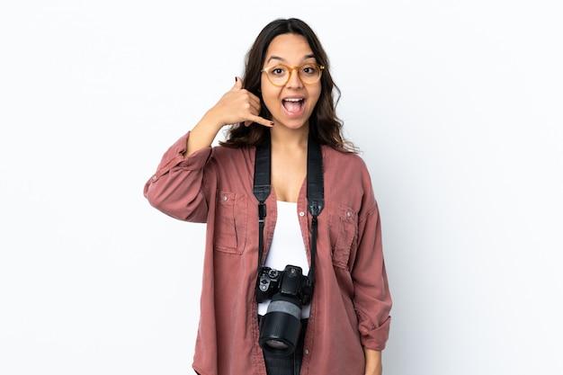 Молодая женщина фотографа над белой стеной делая жест телефона. перезвони мне знак