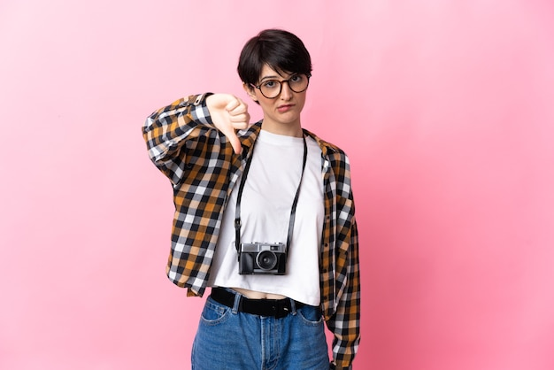 Young photographer woman on pink showing thumb down with negative expression