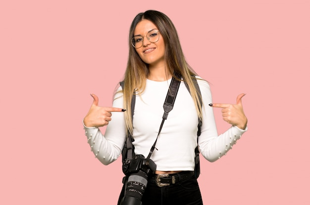 Young photographer woman proud and self-satisfied in love yourself concept on isolated pink background