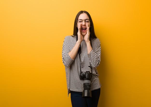 Молодой фотограф женщина кричит что-то счастливое на фронт