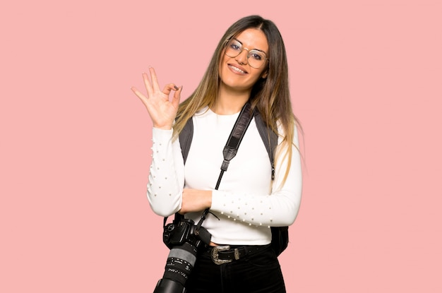 Young photographer woman showing an ok sign with fingers on isolated pink wall