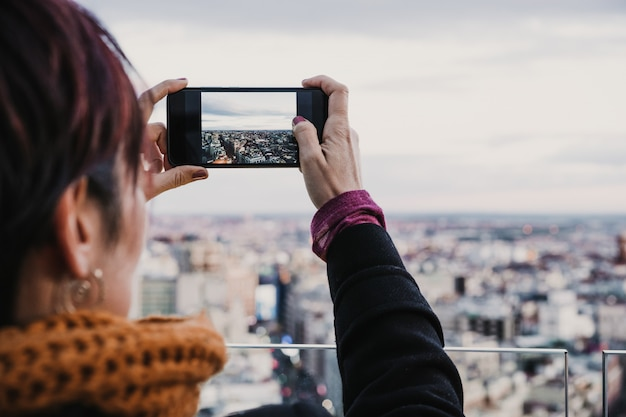 Young photographer woman taking a picture of madrid city from a high rooftop. travel, technology