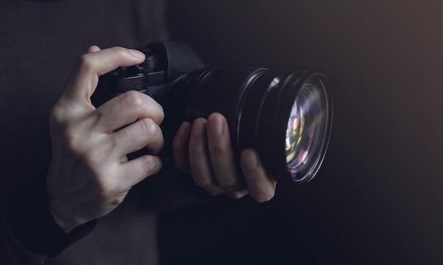 카메라를 사용 하여 사진을 찍는 젊은 사진 작가 여자. 어두운 톤. 손에 선택적 초점