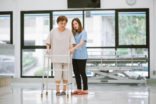 재활 동안 워커를 사용하여 노인 환자를 돕는 젊은 물리 치료사