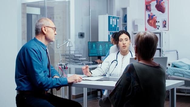 Молодой врач консультирует пожилую пару пенсионеров по поводу их проблемы. обследование в современной больнице или частной клинике для профилактики заболеваний и проблем со здоровьем. жалобы пациентов и медицинская помощь
