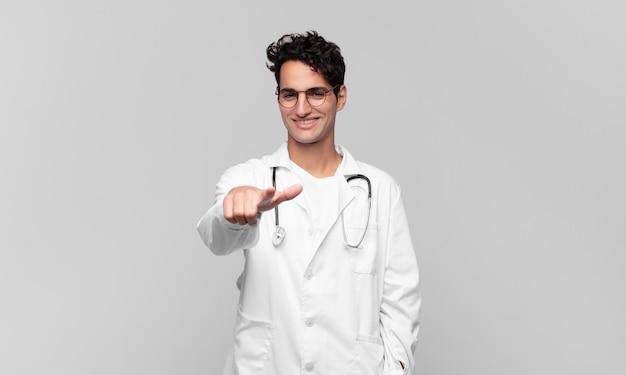 満足し、自信を持って、フレンドリーな笑顔で正面を指して、あなたを選ぶ若い医師