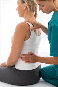 허리 문제가 있는 환자를 돕는 젊은 물리치료사