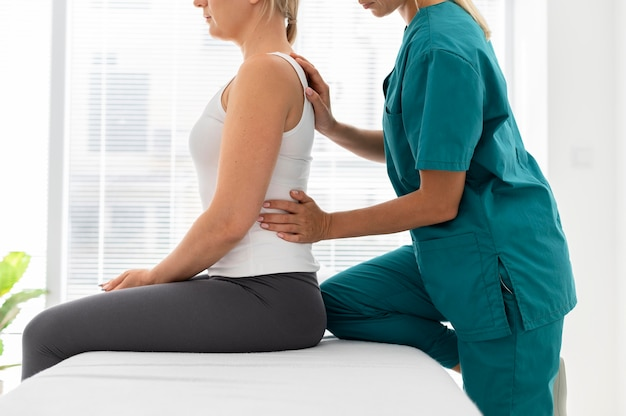 Young physiotherapist helping a patient with back problems