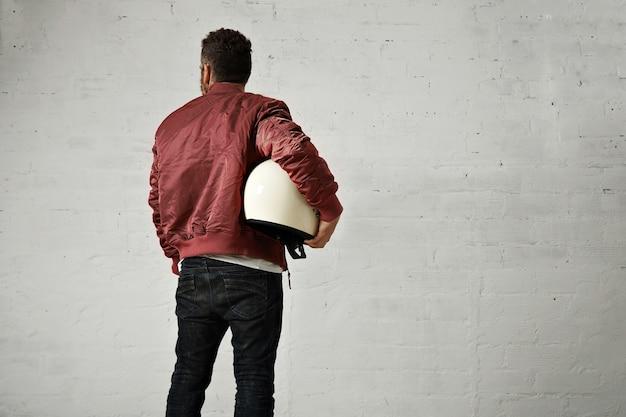 ジーンズの若いパイロット、光沢のあるナイロンバーガンディボンバージャケット、白い壁の背景に後ろから撃たれた彼の腕の下の丸い白いヘルメット