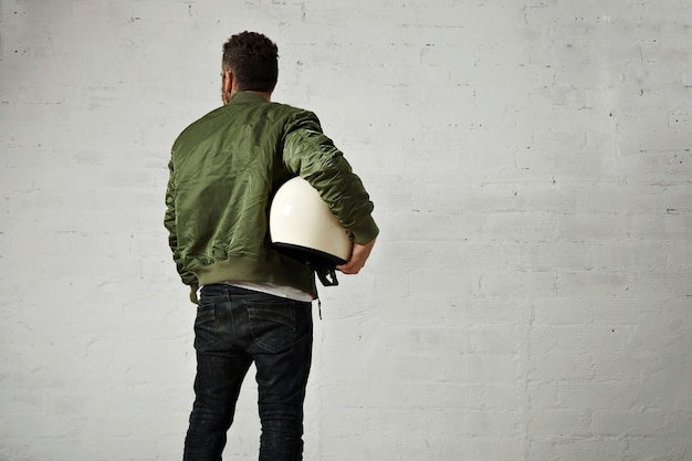 Young pilot in jeans, green bomber jacket and a round white helmet under his arm portrait from the back on white wall
