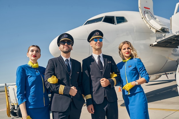 Young pilots in sunglasses and female flight attendants looking into the distance