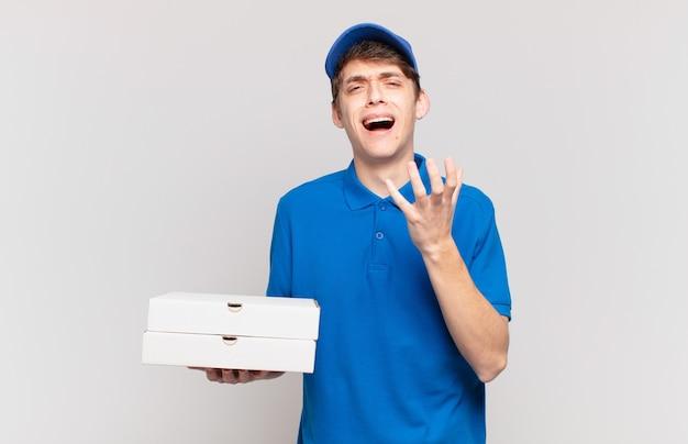 Молодой мальчик-доставщик пиццы выглядит отчаянным и расстроенным, напряженным, несчастным и раздраженным, кричит и кричит