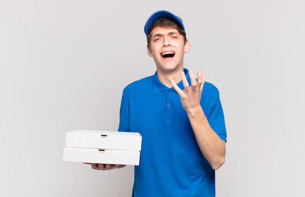 Young pizza deliver boy looking desperate and frustrated, stressed, unhappy and annoyed, shouting and screaming