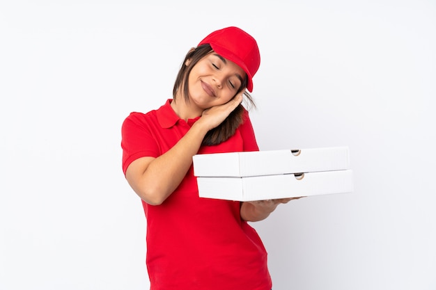 Young pizza delivery girl over isolated white wall making sleep gesture in dorable expression