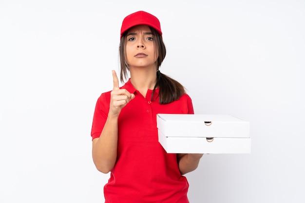 Молодая доставщица пиццы на изолированном белом фоне разочарована и указывает на фронт