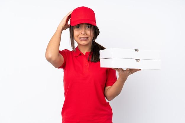 孤立した白い背景の上の若いピザ配達の女の子はイライラし、頭に手を取ります