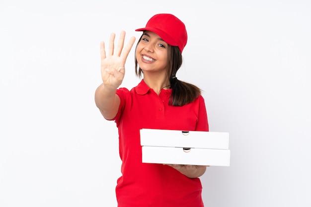 Молодая доставщица пиццы на изолированном белом фоне счастлива и считает четыре пальцами