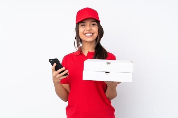 テイクアウトするコーヒーと携帯電話を保持している孤立した白い背景の上の若いピザ配達の女の子