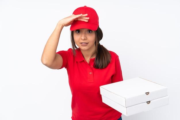 뭔가를 찾고 손으로 멀리 찾고 격리 된 흰색 배경 위에 젊은 피자 배달 소녀