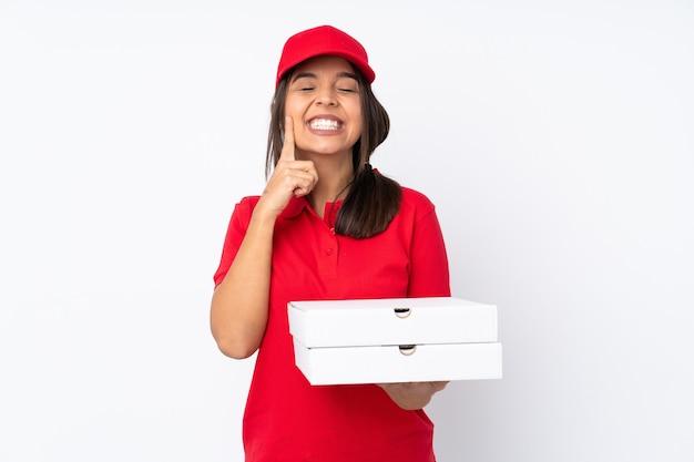 幸せで楽しい表情で笑みを浮かべて孤立した白い背景の上の若いピザ配達の女の子