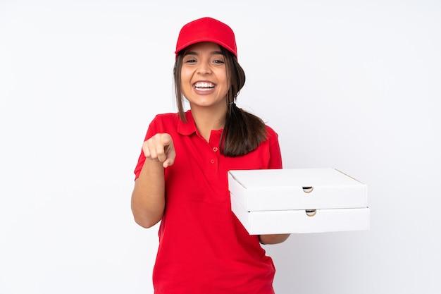 孤立した白い背景の上の若いピザ配達の女の子は驚いて正面を指しています