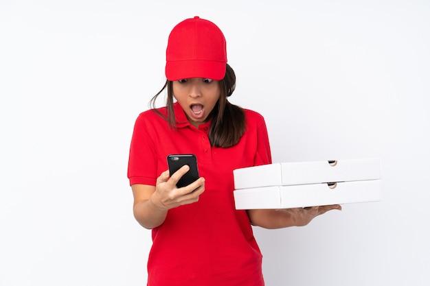 격리 된 흰색 배경 위에 젊은 피자 배달 소녀 놀라게 하 고 메시지를 보내는