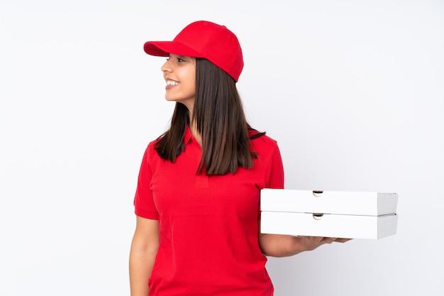 孤立した白い壁の側を見て若いピザ配達の女の子