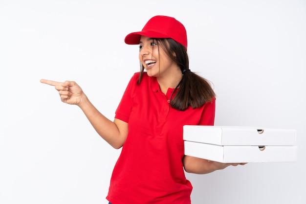 격리 된 흰 벽 측면에 손가락을 가리키고 제품을 제시하는 동안 젊은 피자 배달 소녀