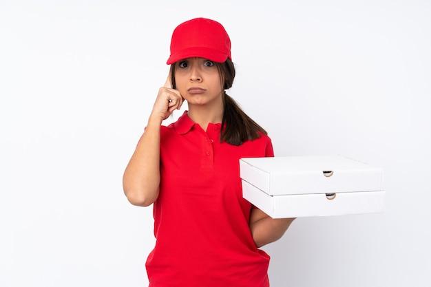 アイデアを考えて孤立した白い壁の上の若いピザ配達の女の子