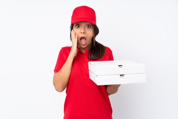 놀라움과 충격을받은 표정으로 격리 된 흰 벽 위에 젊은 피자 배달 소녀