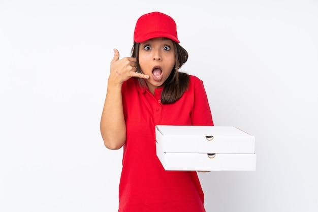 電話のジェスチャーをして疑っている白の上の若いピザ配達の女の子