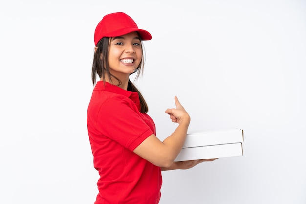 Young pizza delivery girl over white pointing back